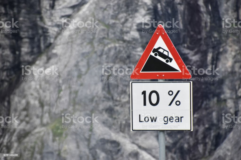 steep hill downwards traffic sign against rock face stock photo