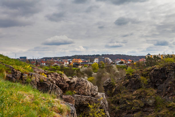 Steep rocks of park Divoka Sarka in Prague, spring time. Wild nature park in the city. Houses at the background. stock photo