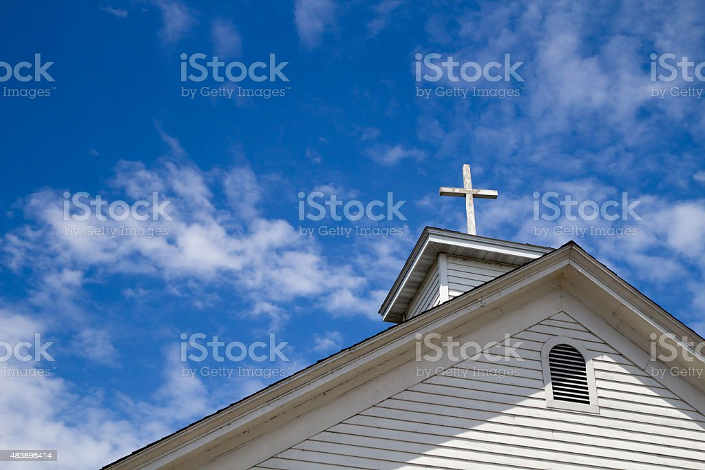 Steeple And Cross Set Against A Blue Sky stock photo