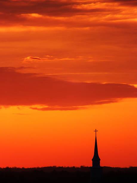 kirchturmspitze in der orange licht der morgendämmerung - kirchturmspitze stock-fotos und bilder