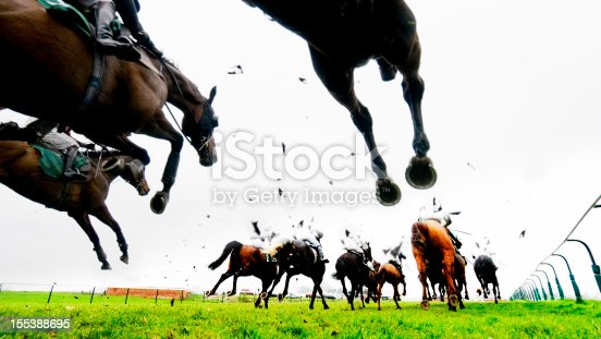Steeplechase and Horse Racing with horses and jockies running into the distance. Low angle view, high contrast image, bleached look with added grain.
