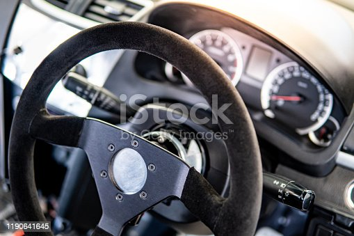 Black steering wheel and dashboard of racing car. Auto interior design concept