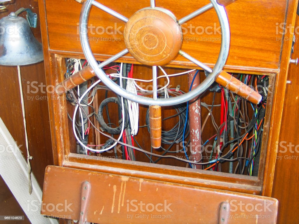 Steering wheel and exposed wiring inside helm of old wooden boat stock photo
