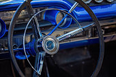 Close up of steering wheel and interior of blue custom classic vintage car
