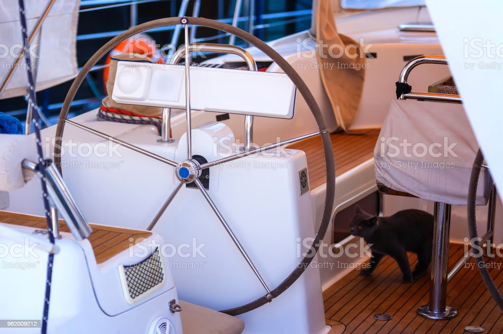 steering wheel on boat with empty seats stock photo