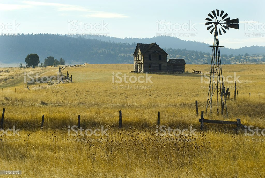 Steinbeck homestead w/ windmill and fence stock photo