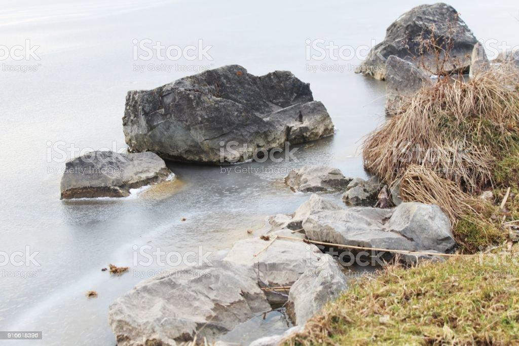 Steine am gefrorenen Seeufer im Winter stock photo