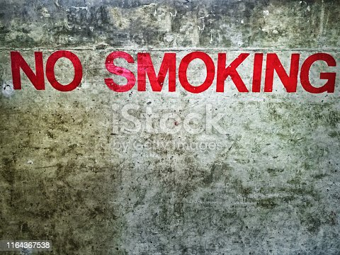 No Smoking sign on a highly textured raw concrete wall.