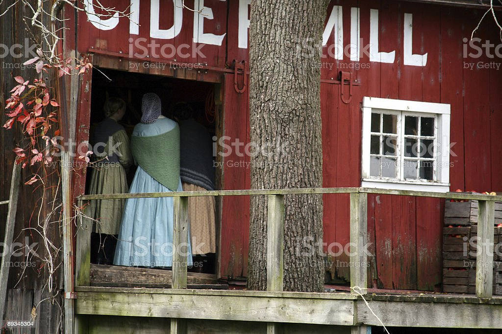 Step Back in Time: 1800s women crowd into cider mill stock photo