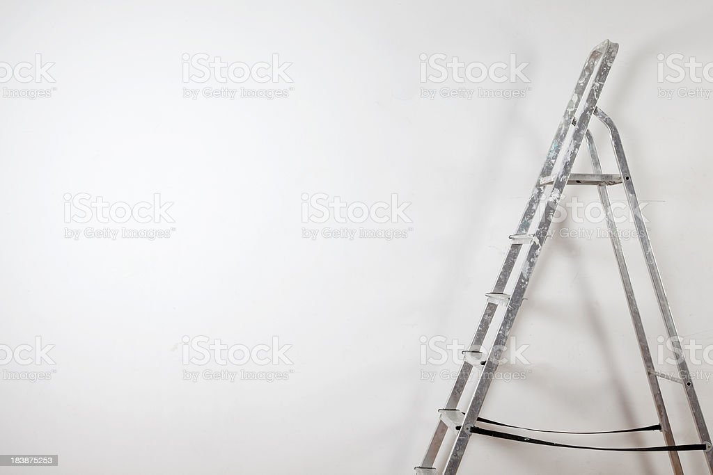 Step ladder against blank wall royalty-free stock photo