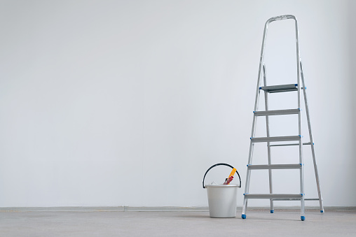 Ladder and bucket with paint roller on a white wall background with copy space. Under construction concept background.