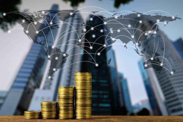 Şehir arka plan ve Dünya Haritası, küresel ağ iş bankacılık kavramı ile en iyi ahşap çalışma masa üzerinde adım sikke yığını. stok fotoğrafı