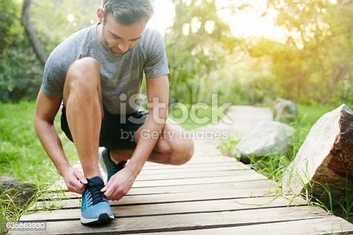 Shot of a young man tying his laces while out for a run in the park