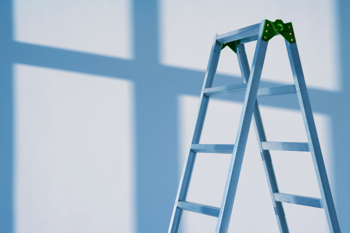 Step-ladder near the wall to paint. Dramatic evening light and shadows from the window.
