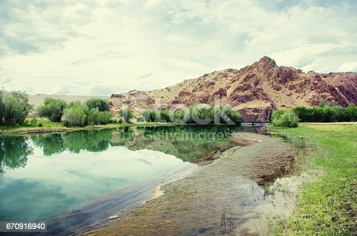 istock Steppe crystal clear lake with algae with groves of trees with the hill and red rocks in the background under a beautiful sky Altai, Siberia, Russia 670916940