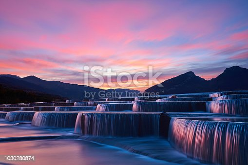 Side view of stepped waterfall group at sunrise in pink sky.