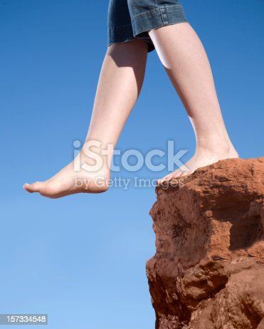 A pair of feet step off the edge into the void.