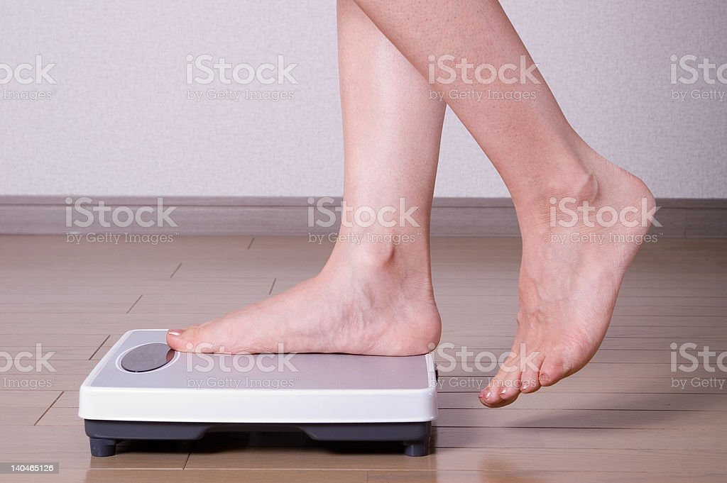 Stepping on scales stock photo