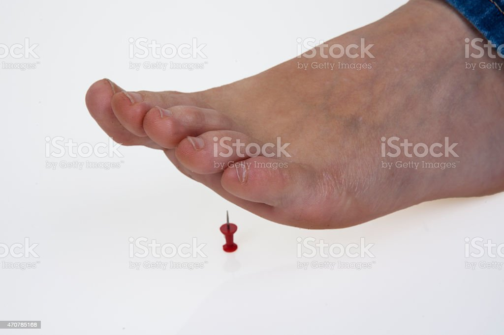 Stepping on the pushpin stock photo