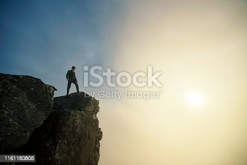 Side Angle low angle view of a businessman at sunset on top of a cliff with dramatic sky and clouds below and above Cape Town South Africa