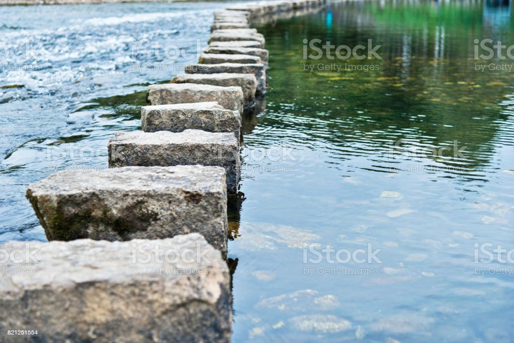 Stepping stones on the water stock photo