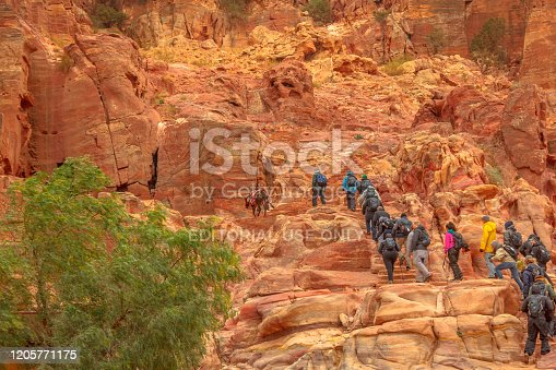 Petra, Jordan - Jan 4, 2020: tourists, Bedouins and mules climb the 850 steps to reach Al-Deir, alias the Monastery, the largest and most distant monument of Petra. Steps carved out of sandstone rock.