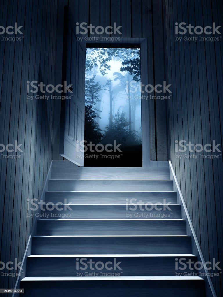 Steps leading from a dark basement to open the door stock photo