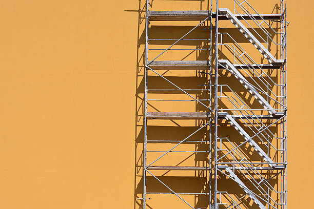 Steps of a scaffold Scaffold beside an ocher colored building.  scaffolding stock pictures, royalty-free photos & images