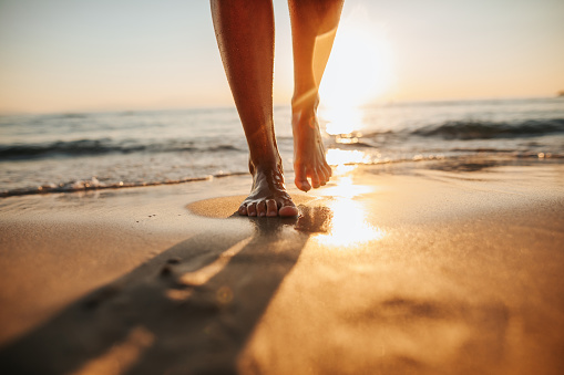 Close-up of female legs getting out of the sea water and walking on sandy beach at beautiful sunset
