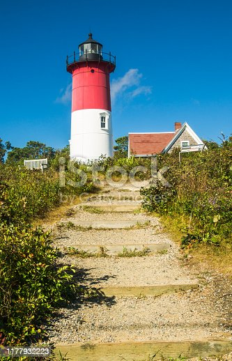 a rustic stairway on the path leads to the famous red and white tower of the Nauset Lighthouse on Cape Cod.