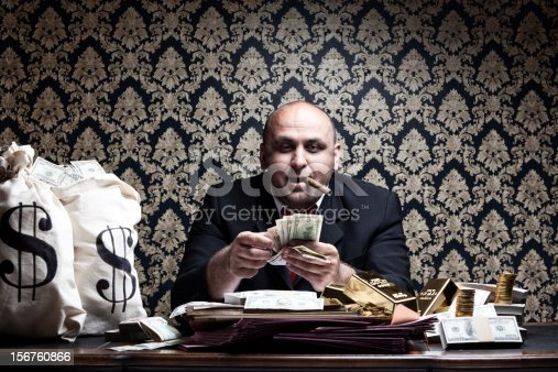 istock Stereotype Rich Man Posing With Money Bags,Counting Dollar Bills 156760866