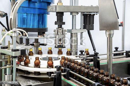 istock Sterile bottles on the production line conveyor of the pharmaceutical industry. Machine for liquid drugs glassware bottling. 1015863790