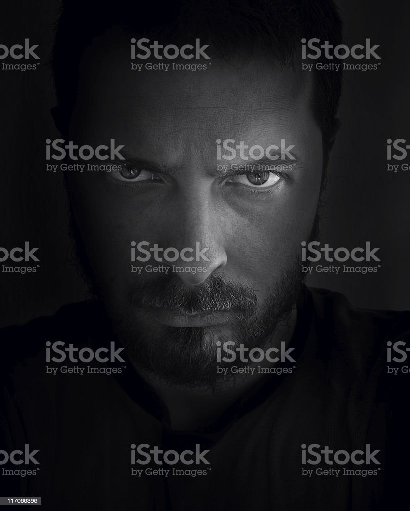 A stern face hidden in the shadows of a black background stock photo