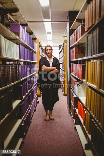 1070981872istockphoto Stern lawyer standing between shelfs with arms crossed 538203017