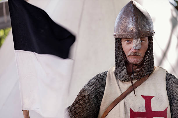 stern looking knight holding a regimental flag. - the crusades stock photos and pictures