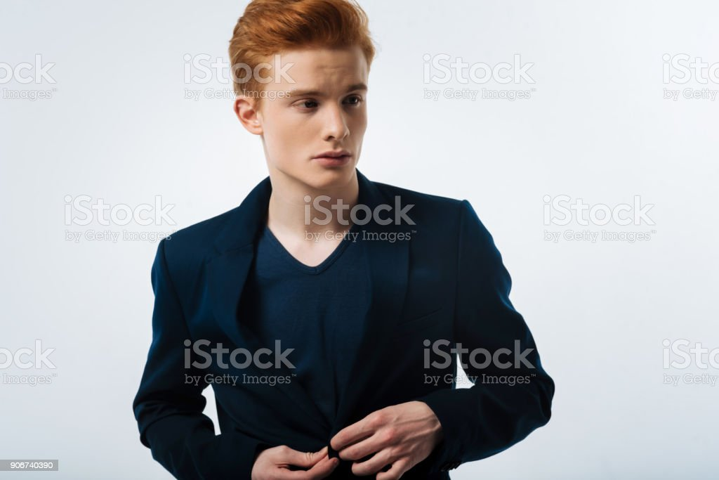Stern man buttoning his jacket up stock photo