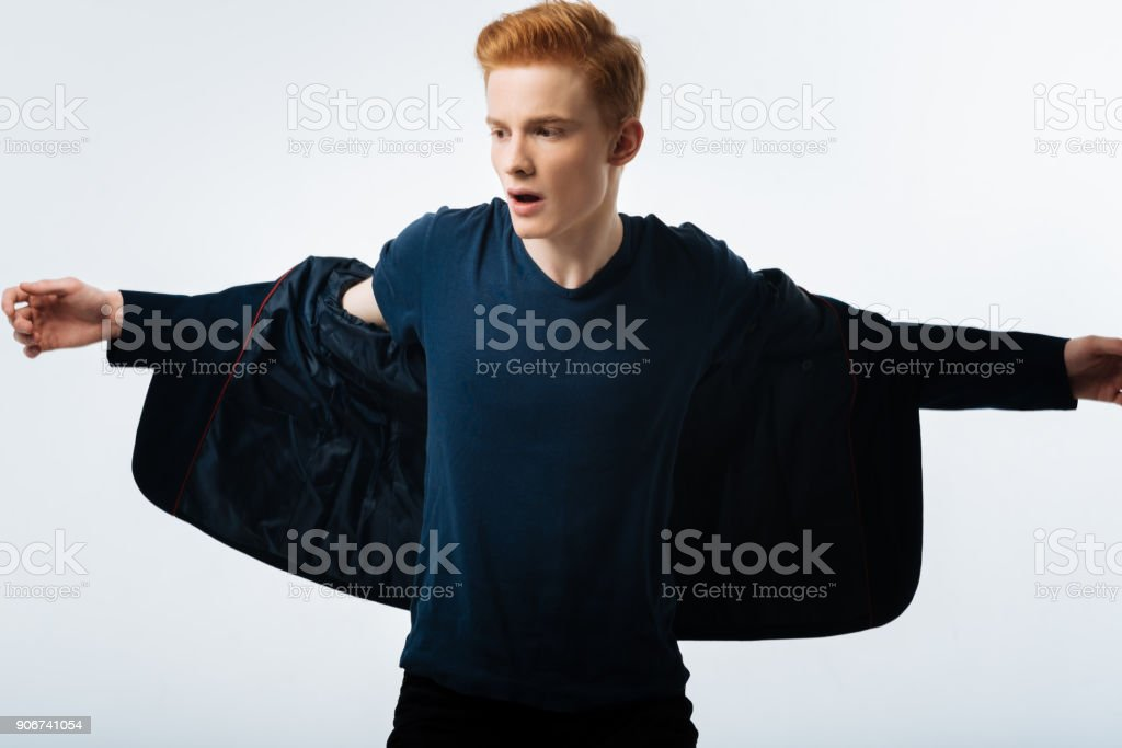 Stern man taking his jacket off stock photo