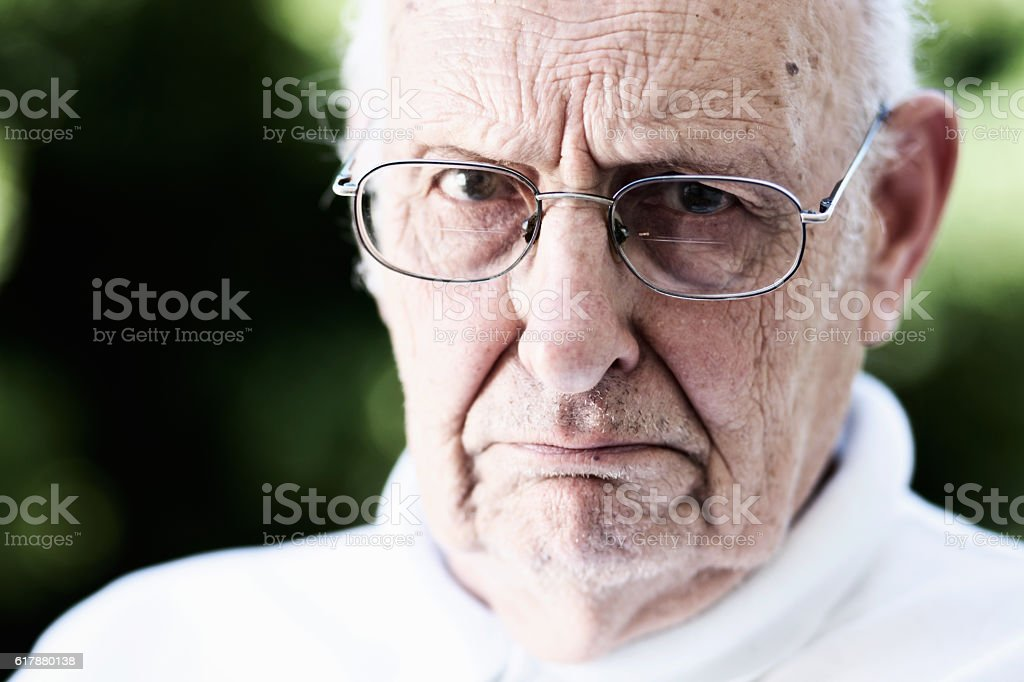 Stern old man glares over his spectacles: grumpy old man stock photo
