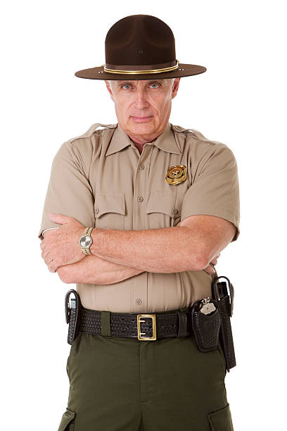 Stern Police Officer Portrait of a mature law enforcement officer standing with his arms folded, solated on a pure white background. trooper stock pictures, royalty-free photos & images