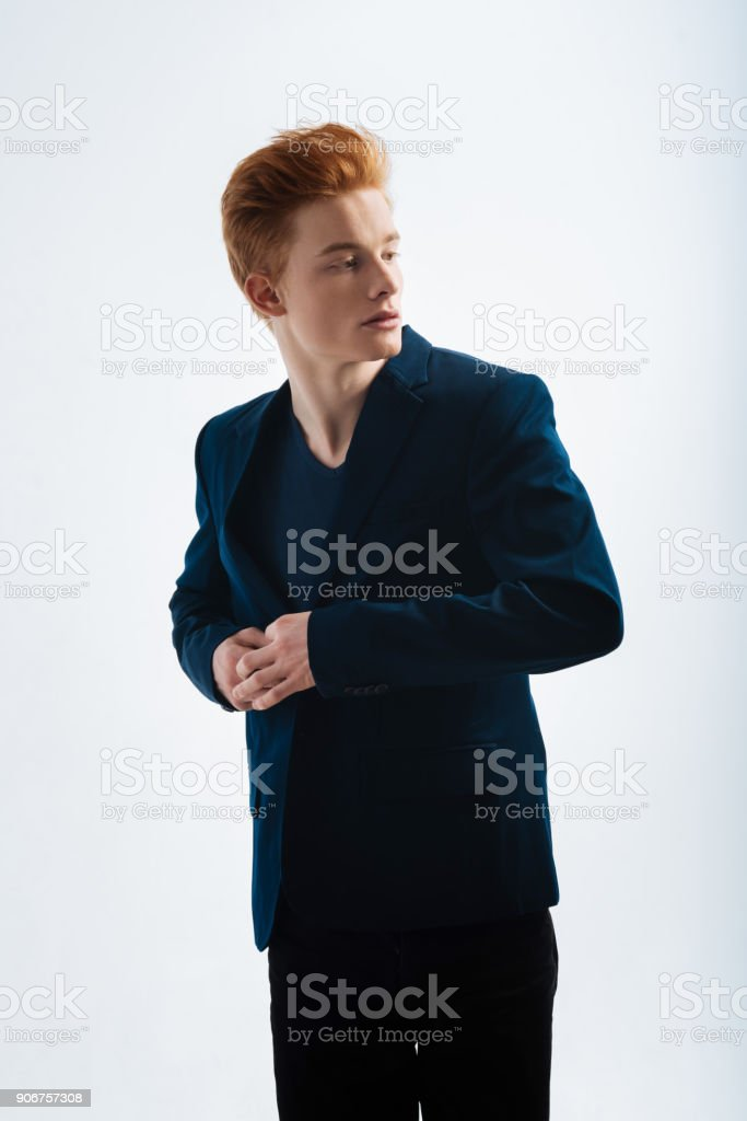 Stern red-headed man looking over his shoulder stock photo