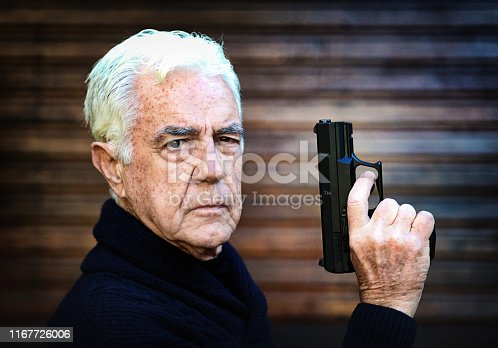 A seriously-looking senior man holds up his pistol and glares at the camera.