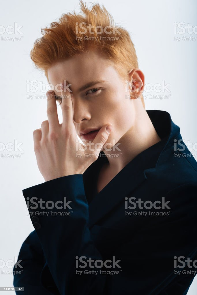Stern young man touching his forehead stock photo