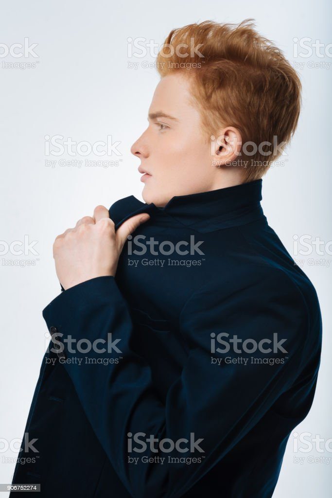 Stern young man touching his jacket stock photo