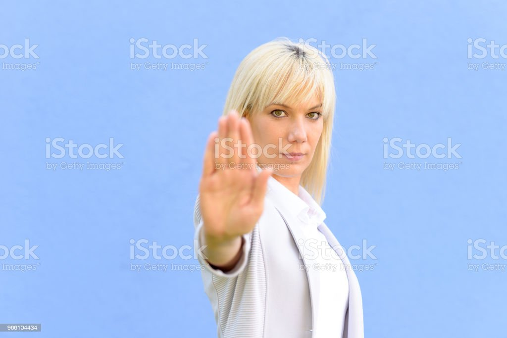 Stern young woman making a stop gesture - Royalty-free Adult Stock Photo
