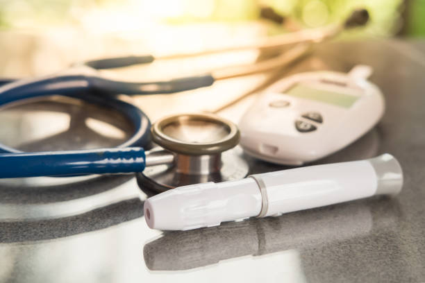 Stethoscope and blood glucose meter, lancet on the wooden table.Healthcare medical and check up, diabetes, glycemia, and people concept. Flat lay. stock photo