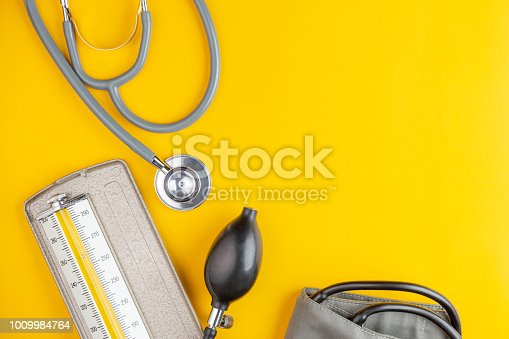 stethoscope and blood pressure on yellow background with copy space, health care and medical concept