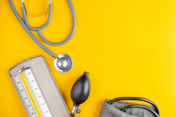 stethoscope and blood pressure stethoscope and blood pressure on yellow background with copy space, health care and medical concept blood pressure gauge stock pictures, royalty-free photos & images