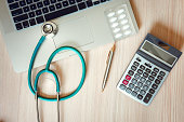 istock Stethoscope and Calculator on Doctor Office Table., Table Workspace Desktop for Examining Patient Health., Business Healthcare Insurance and Medicine Concept. 1130839266
