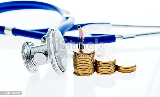 Stethoscope and coins on white background.