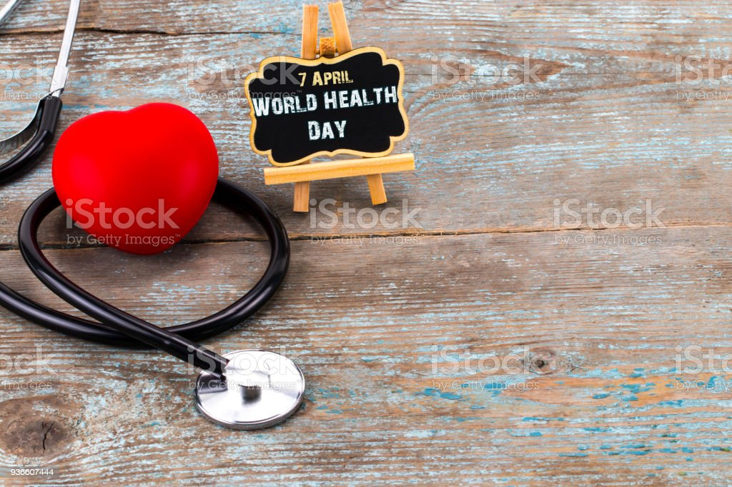 Stethoscope and heart symbol with inscription World Health Day on wooden background with copy space stock photo